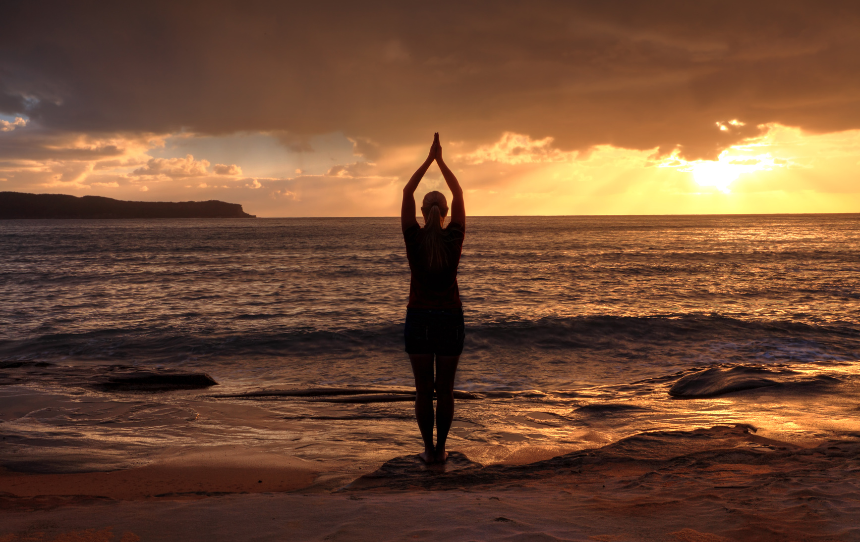 Female relaxing at sunrise, performing tadasana - mountain pose by the sea at sunrise