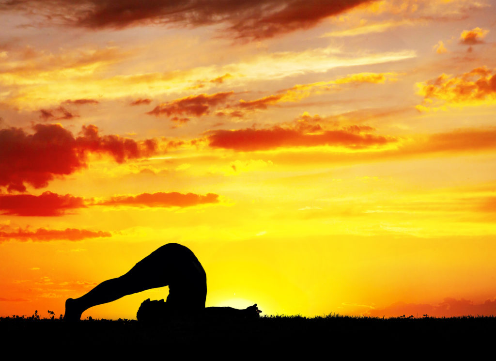 Yoga Halasana plough inverse pose by Man in silhouette with orange sunset sky background. Free space for text