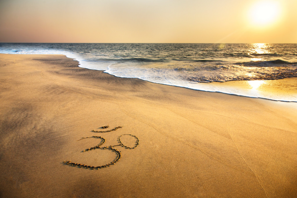 Om symbol on the sand at the beach near the ocean