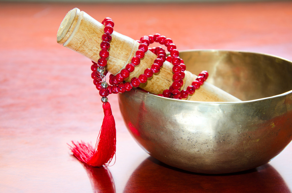 Closeup of a tibetan bowl and red  mala beads for meditation on wooden background.