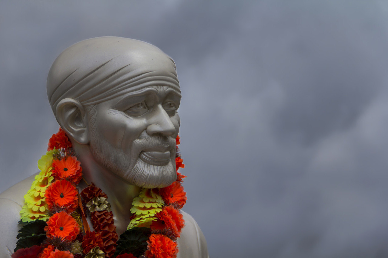 Sai Baba face in a grey sky background