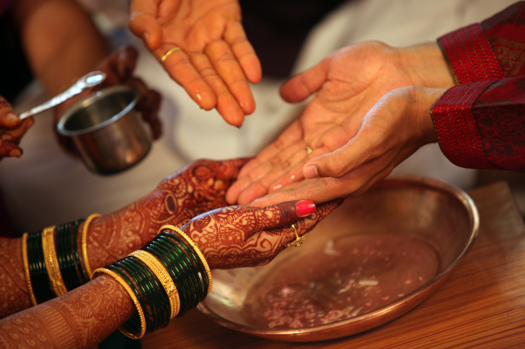 The hands of bride and groom being washed with holy water in a traditional Hindu wedding ritual