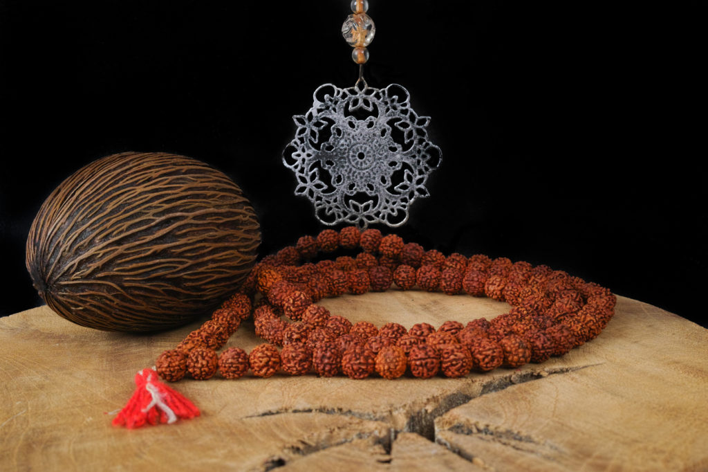 Indian art - tin mandala, prayer beards from Rudraksha, Foxtail palm seed on teak wood and black background