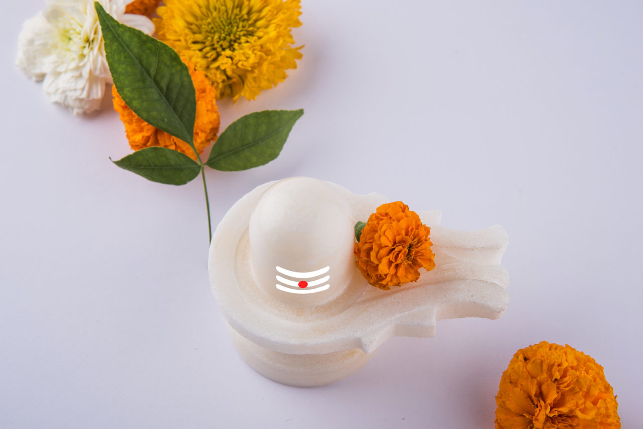 Shiva Linga made up of white marble decorated with flowers & bael leaf known as Aegle marmelos, over white background, maha shiva ratri a festival of hindu God shankar or shankar bhagwan or bholenath